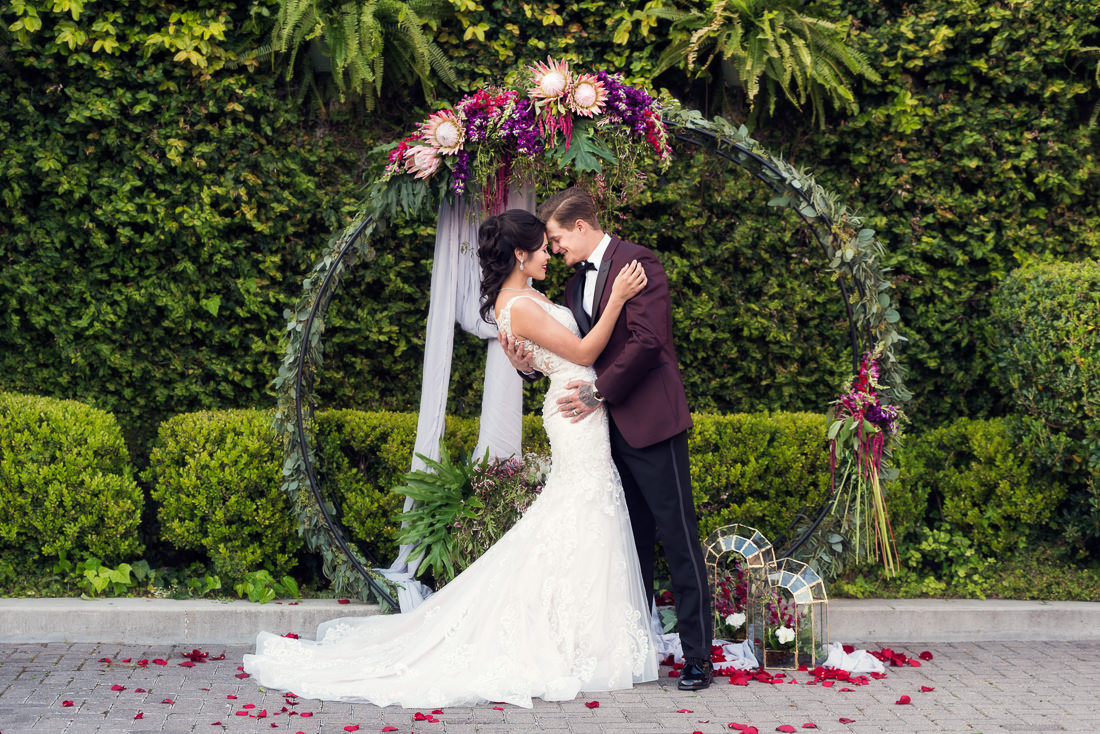 best wedding photographer Pensacola Orlando | creative imagery by Lazzat Photography | wedding floral green arch gorgeous bride and groom in burgundy suit