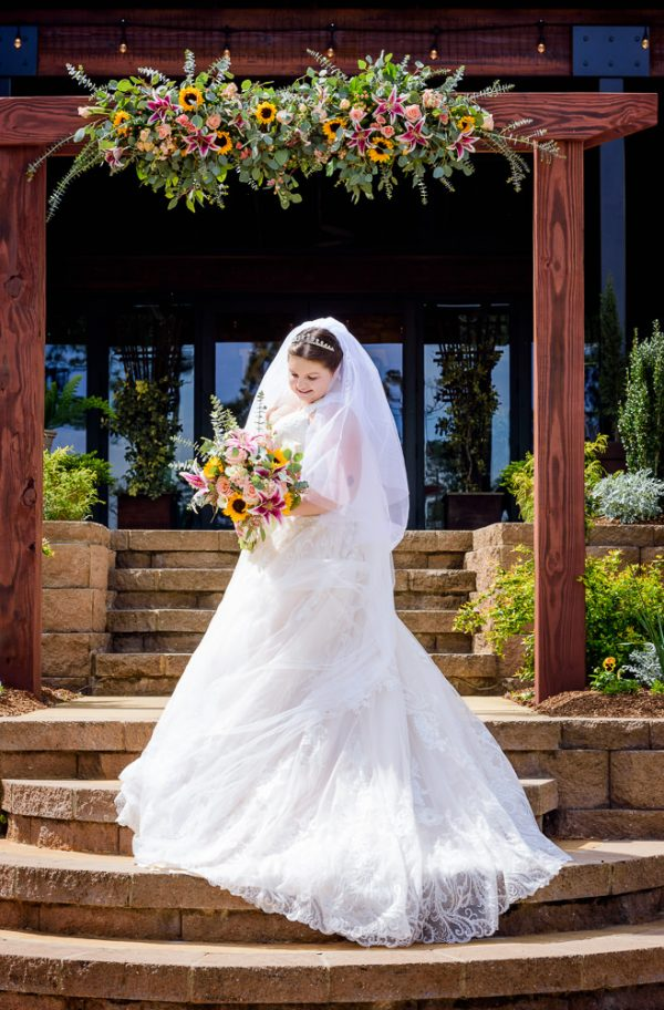 Bride under her wedding arch, Coldwater Gardens, Rustic Fairy Tale Wedding, Lazzat Photography