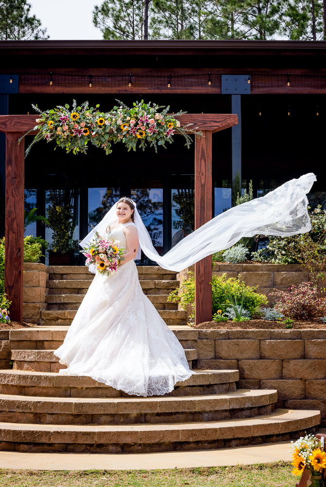 Bride under her wedding arch with veil blowing in the wind, Coldwater Gardens, Rustic Fairy Tale Wedding, Lazzat Photography