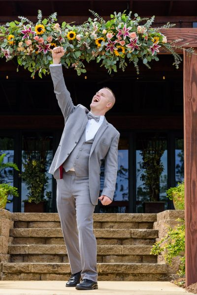 Groom fist pumping under the wedding arch, Coldwater Gardens, Rustic Fairy Tale Wedding, Lazzat Photography