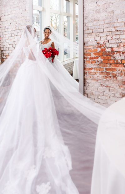 Carla looking in the mirror at 5Eleven Palafox, Romantic Red Rose Wedding, Lazzat Photography