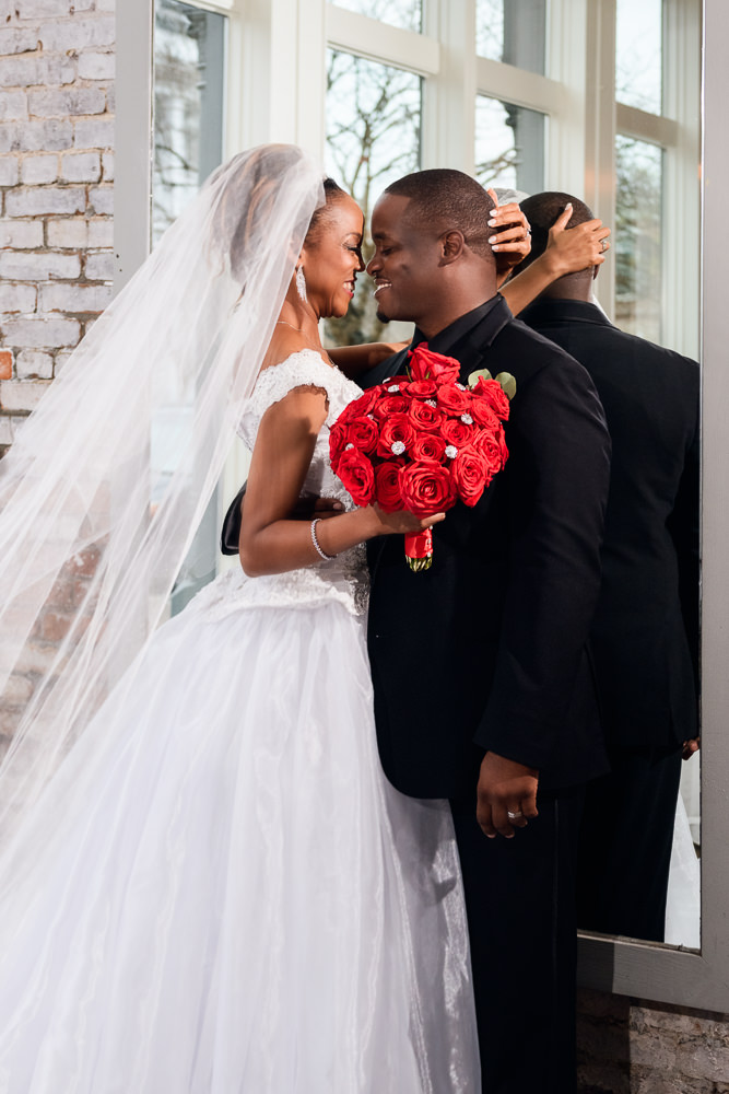 Carla and Lorenzo looking at each other in front of the mirror at 5Eleven Palafox, Romantic Red Rose Wedding, Lazzat Photography