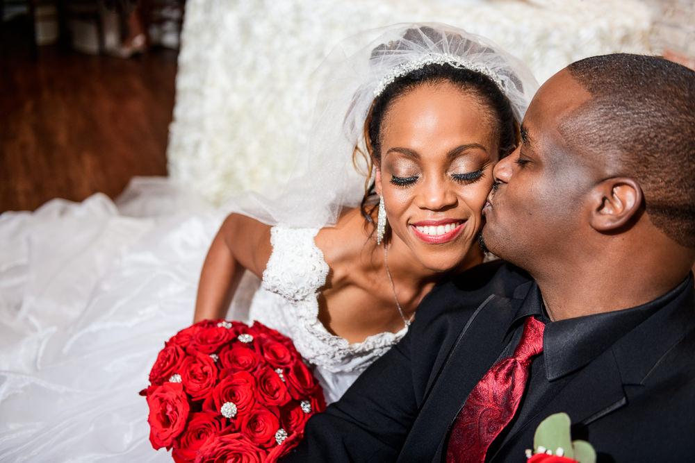 Lorenzo kissing Carla on the cheek, 5Eleven Palafox, Romantic Red Rose Wedding, Lazzat Photography