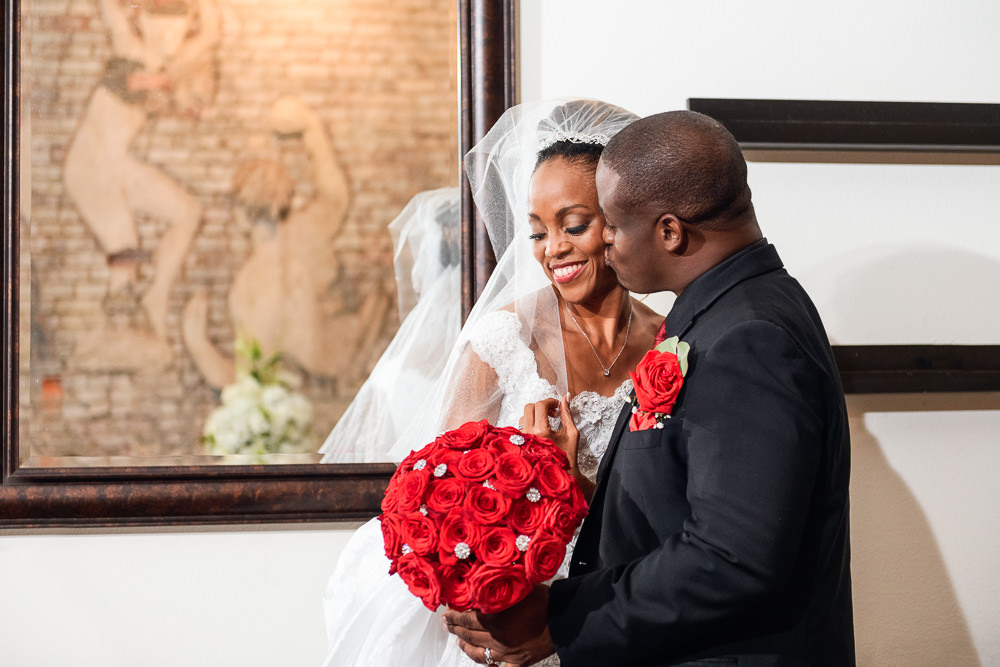 Lorenzo kissing Carla on the cheek in front of the mirror, 5Eleven Palafox, Romantic Red Rose Wedding, Lazzat Photography