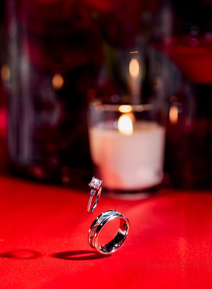 Carla + Lorenzo's rings suspended in the air over the red table, 5Eleven Palafox, Romantic Red Rose Wedding, Lazzat Photography