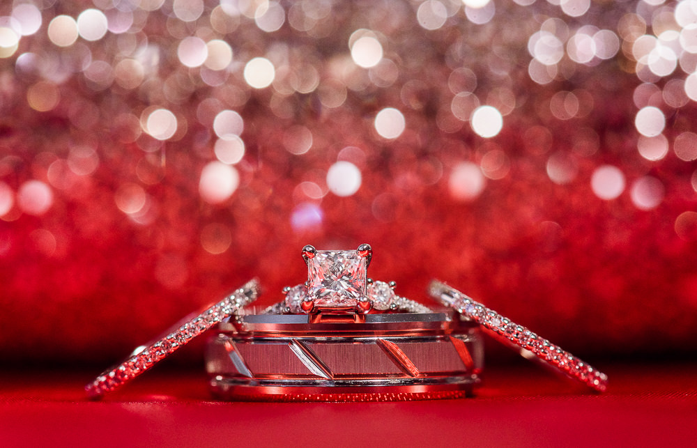 Carla + Lorenzo's rings in front of red glitter, 5Eleven Palafox, Romantic Red Rose Wedding, Lazzat Photography