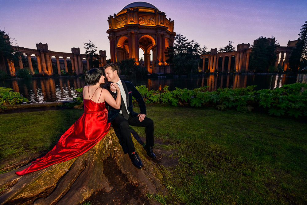 Natalie and Crockett sitting on a rock looking at each other during the Epic Couple's Session at Palace of Fine Arts in San Francisco | Lazzat Photography