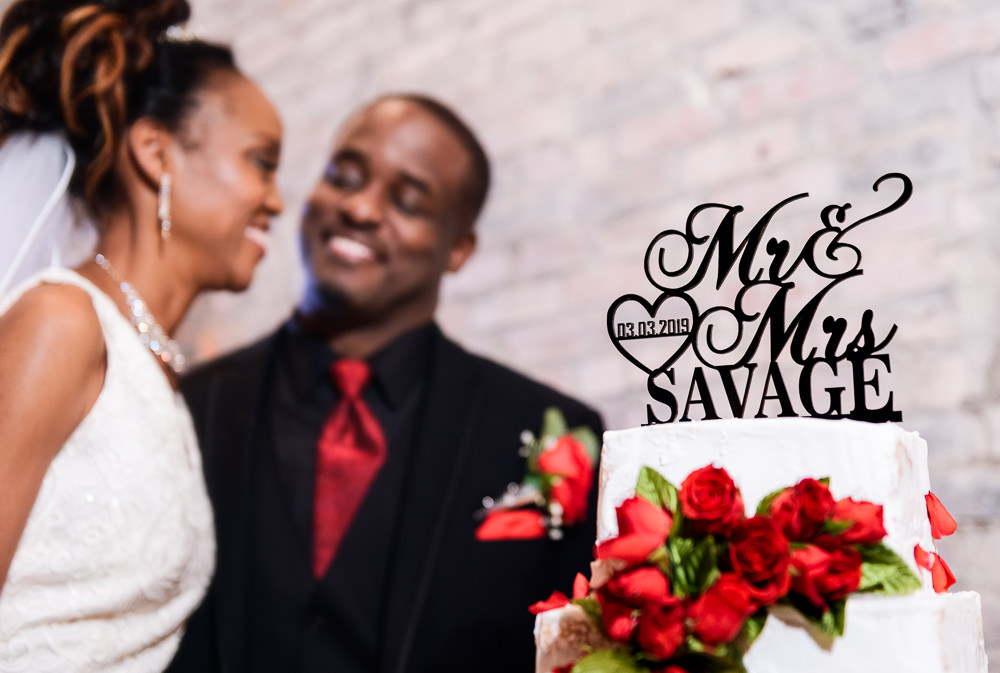 Carla + Lorenzo behind their personalized cake topper and red rose wedding cake, 5Eleven Palafox, Romantic Red Rose Wedding, Lazzat Photography