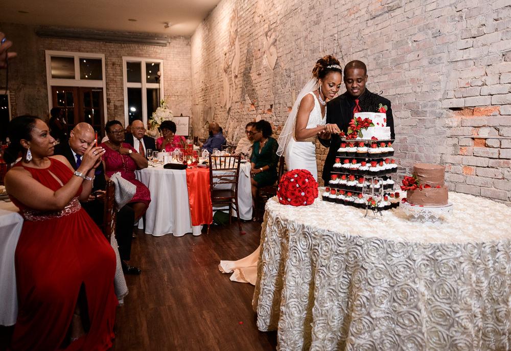 Carla + Lorenzo cutting their red rose wedding cake, 5Eleven Palafox, Romantic Red Rose Wedding, Lazzat Photography
