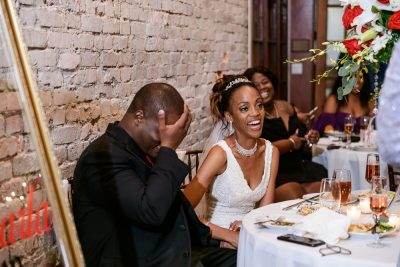 Lorenzo with his hand on his head and Carla laughing during the toasts, 5Eleven Palafox, Romantic Red Rose Wedding, Lazzat Photography