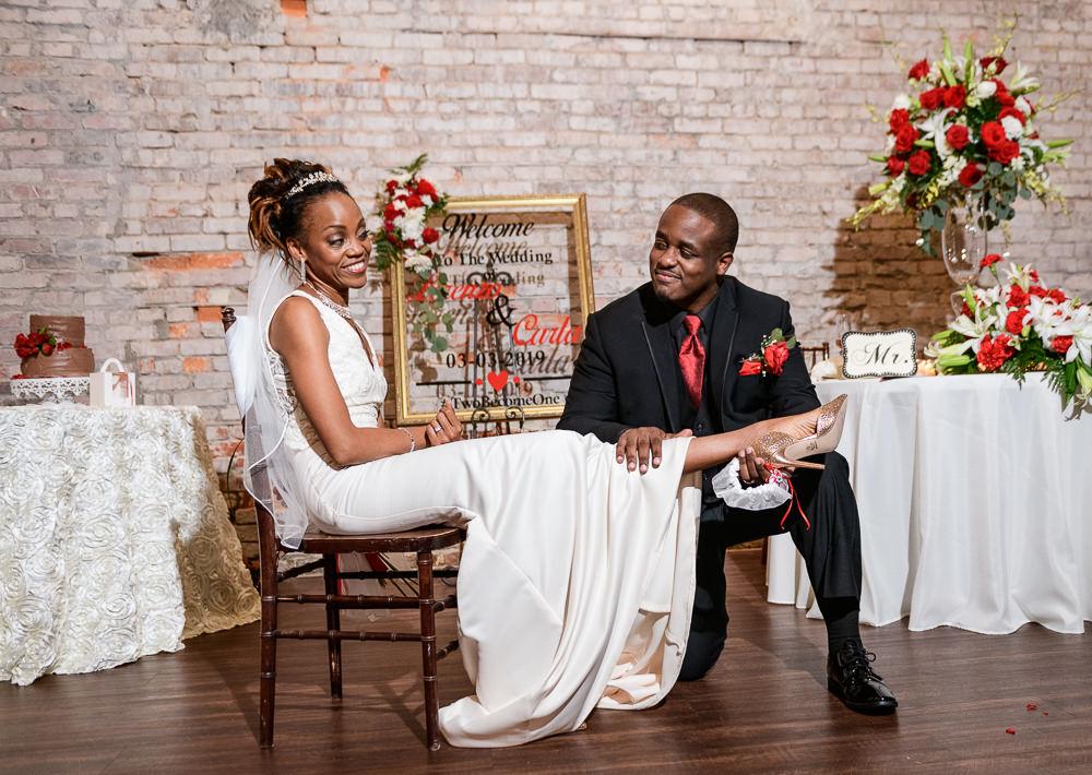 Lorenzo taking off Carla's garter, 5Eleven Palafox, Romantic Red Rose Wedding, Lazzat Photography