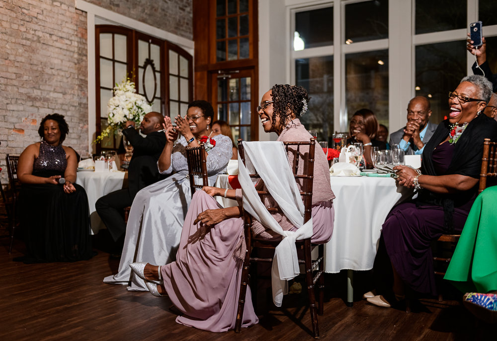 Guests laughing white Lorenzo takes off Carla's garter, 5Eleven Palafox, Romantic Red Rose Wedding, Lazzat Photography