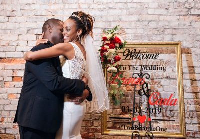 Lorenzo hugging Carla in front of their welcome sign, 5Eleven Palafox, Romantic Red Rose Wedding, Lazzat Photography