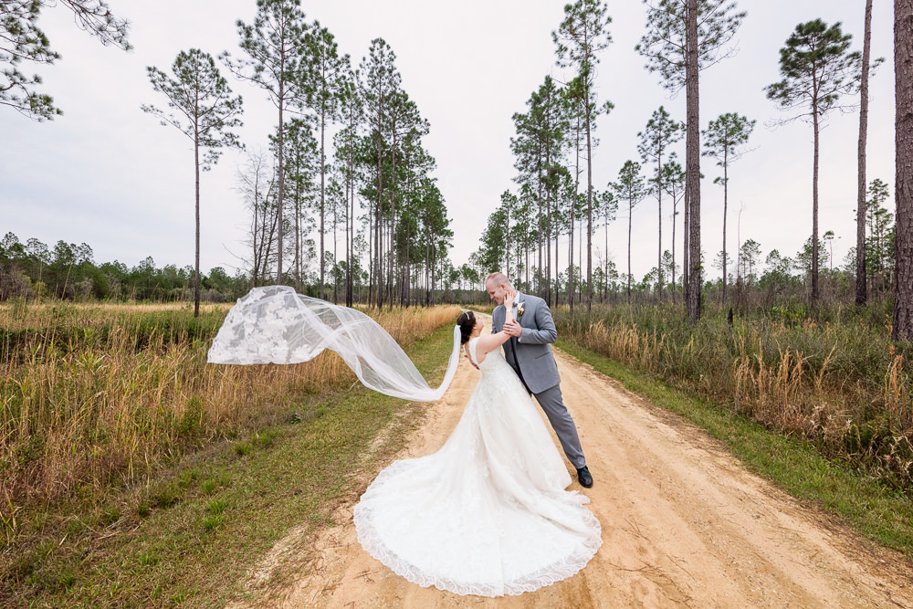 Bride and Groom on a dirt road with Emily's veil blowing in the wind, Coldwater Gardens, Rustic Fairy Tale Wedding, Lazzat Photography