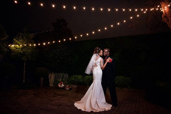Carla + Lorenza under bistro lights outside 5Eleven Palafox, Romantic Red Rose Wedding, Lazzat Photography