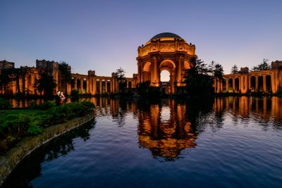 Crockett hugging Natalie and looking into the building's reflection in the water during the Epic Couple's Session at Palace of Fine Arts in San Francisco   Lazzat Photography