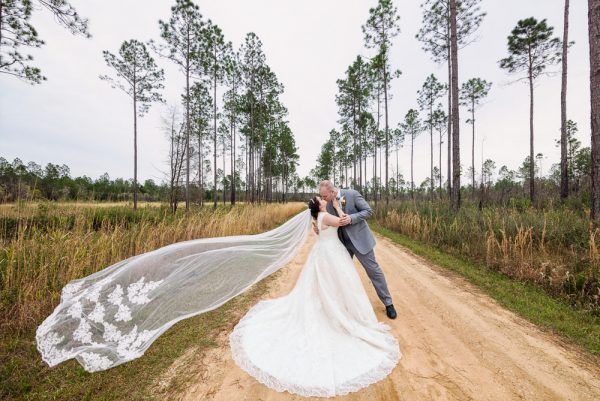 Bride and Groom kissing on a dirt road with Emily's veil blowing in the wind, Coldwater Gardens, Rustic Fairy Tale Wedding, Lazzat Photography