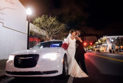 Carla + Lorenza next to their white limo outside 5Eleven Palafox, Romantic Red Rose Wedding, Lazzat Photography