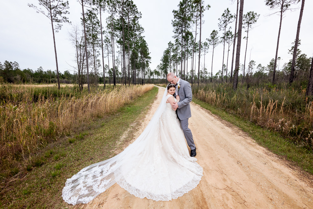 Bride and Groom hugging on a dirt road, Coldwater Gardens, Rustic Fairy Tale Wedding, Lazzat Photography