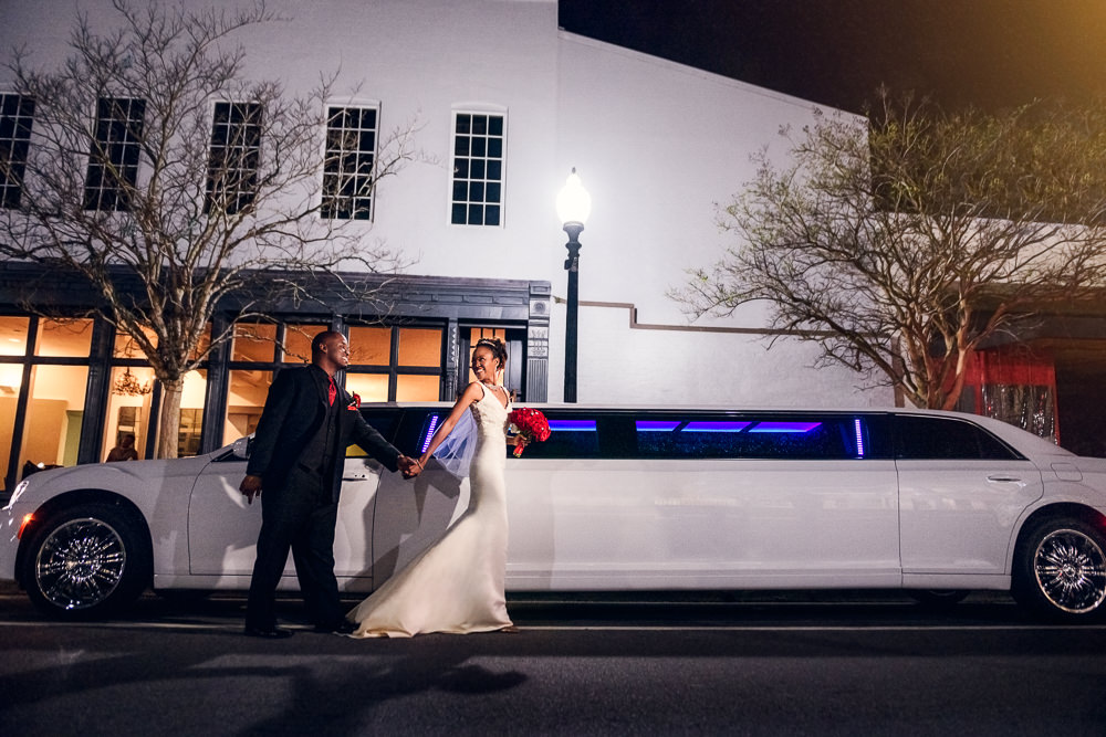 Carla leading Lorenza next to their white limo outside 5Eleven Palafox, Romantic Red Rose Wedding, Lazzat Photography