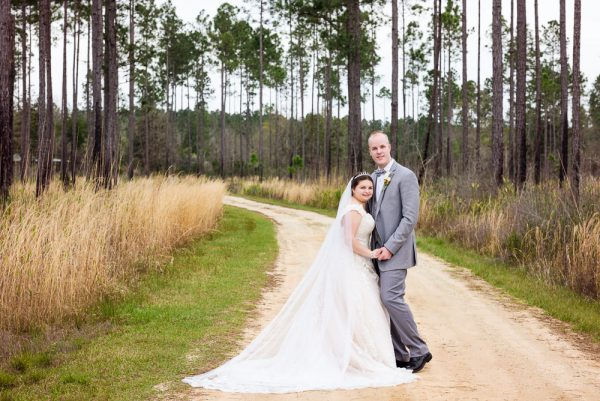Bride and Groom smiling at the camera on a dirt road, Coldwater Gardens, Rustic Fairy Tale Wedding, Lazzat Photography