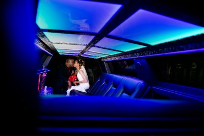 Carla + Lorenza kissing inside their limo with blue lighting, downtown pensacola, Romantic Red Rose Wedding, Lazzat Photography