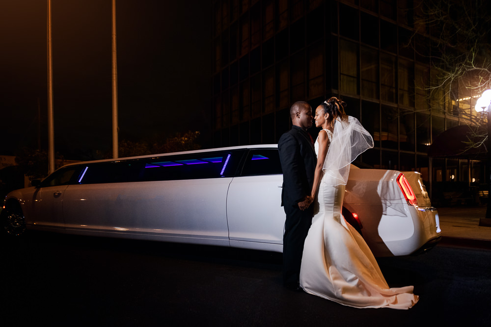 Carla + Lorenza facing each other and holding hands outside their limo, downtown pensacola, Romantic Red Rose Wedding, Lazzat Photography