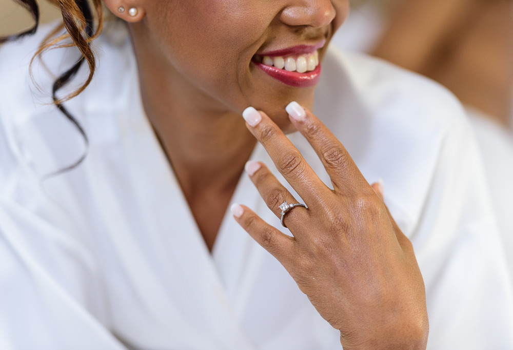 Carla touching her chin showing off her engagement ring at The Pensacola Grand Hotel, Romantic Red Rose Wedding, Lazzat Photography