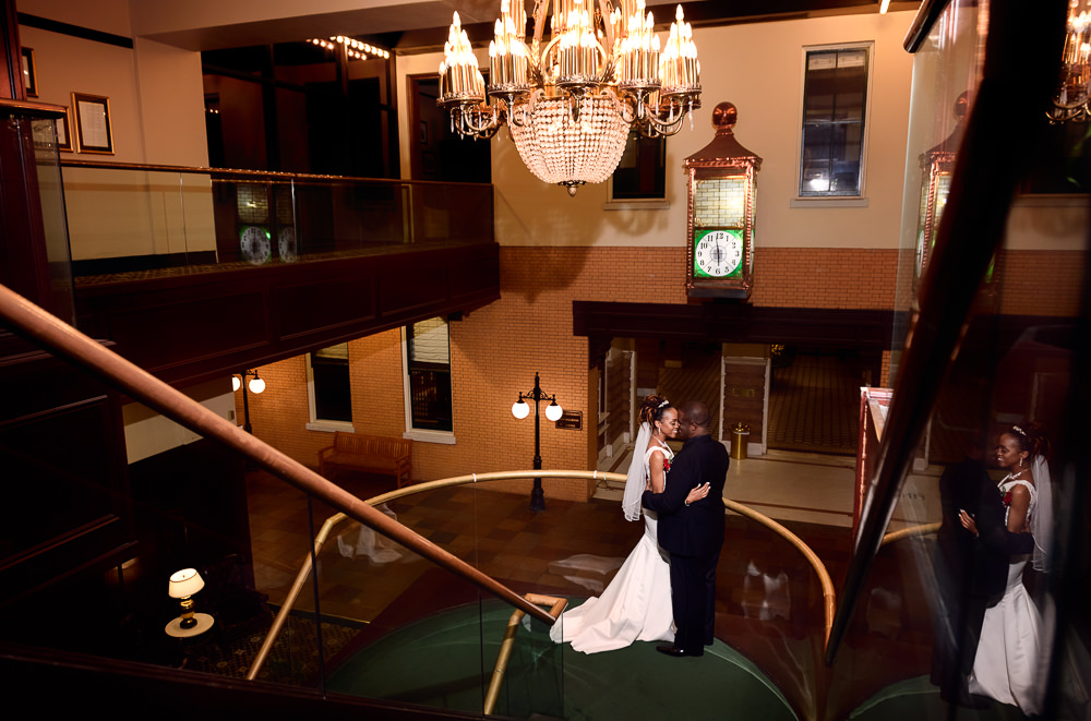 Carla + Lorenza facing each other on the stairs of The Pensacola Grand Hotel, Romantic Red Rose Wedding, Lazzat Photography