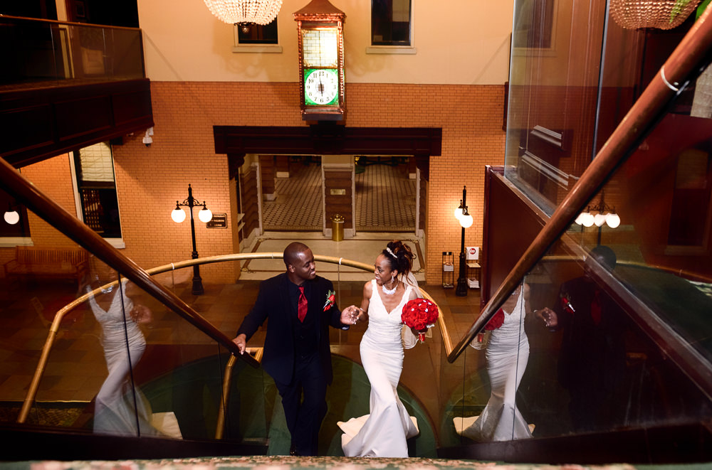 Carla + Lorenza walking up the stairs of The Pensacola Grand Hotel, Romantic Red Rose Wedding, Lazzat Photography