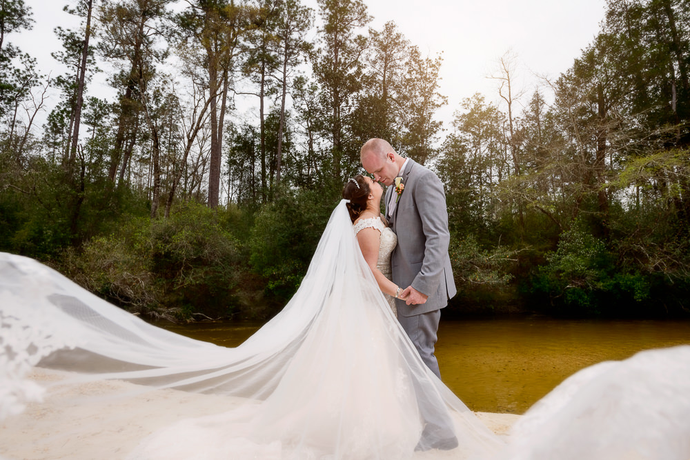 Bride and Groom almost kissing on the beach with Emily's dramatic veil blowing towards the camera, Coldwater Gardens, Rustic Fairy Tale Wedding, Lazzat Photography
