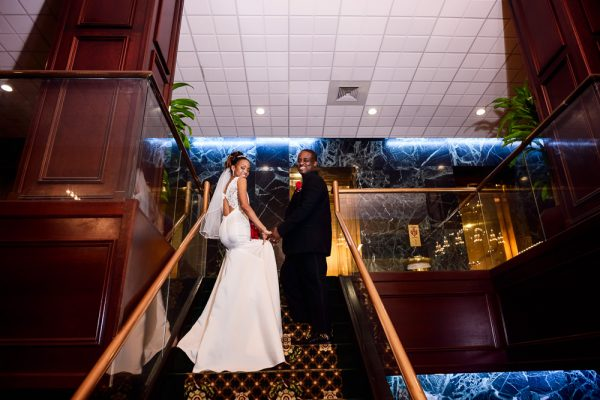Carla + Lorenza looking back down the stairs of The Pensacola Grand Hotel, Romantic Red Rose Wedding, Lazzat Photography