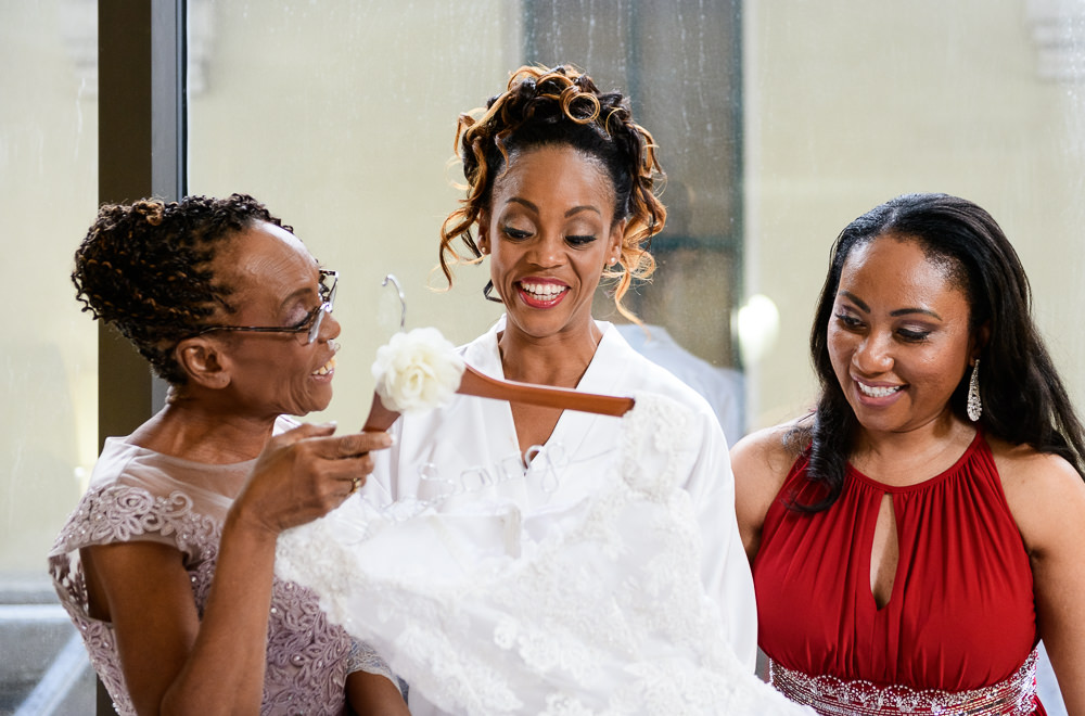 Carla looking at her dress with her mom and sister in law at The Pensacola Grand Hotel, Romantic Red Rose Wedding, Lazzat Photography