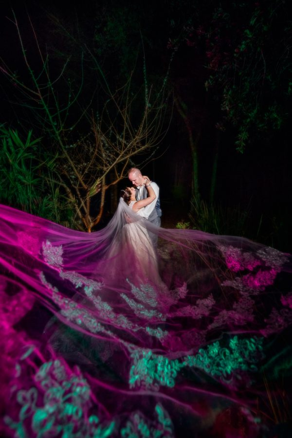 Bride and Groom hugging with Emily's purple and green colored veil flows towards the camera, Coldwater Gardens, Rustic Fairy Tale Wedding, Lazzat Photography