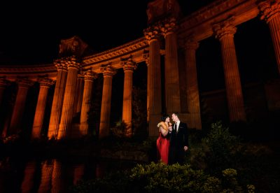 Natalie and Crockett looking at each other under the red columns during the Epic Couple's Session at Palace of Fine Arts in San Francisco   Lazzat Photography