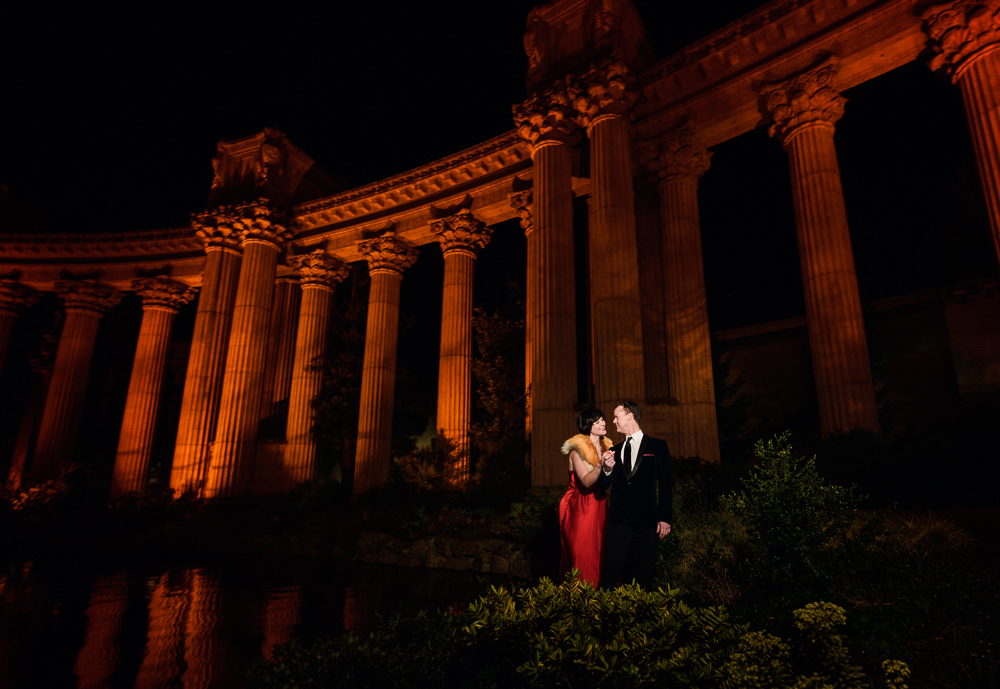 Natalie and Crockett looking at each other under the red columns during the Epic Couple's Session at Palace of Fine Arts in San Francisco | Lazzat Photography
