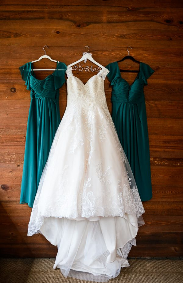 Bride's wedding dress hanging with her green bridesmaid's dresses, Coldwater Gardens, Rustic Fairy Tale Wedding, Lazzat Photography
