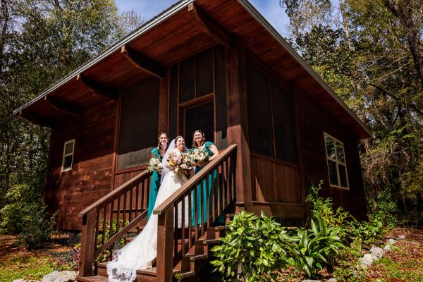 Bride and her bridesmaids on the steps of their cabin, Coldwater Gardens, Rustic Fairy Tale Wedding, Lazzat Photography