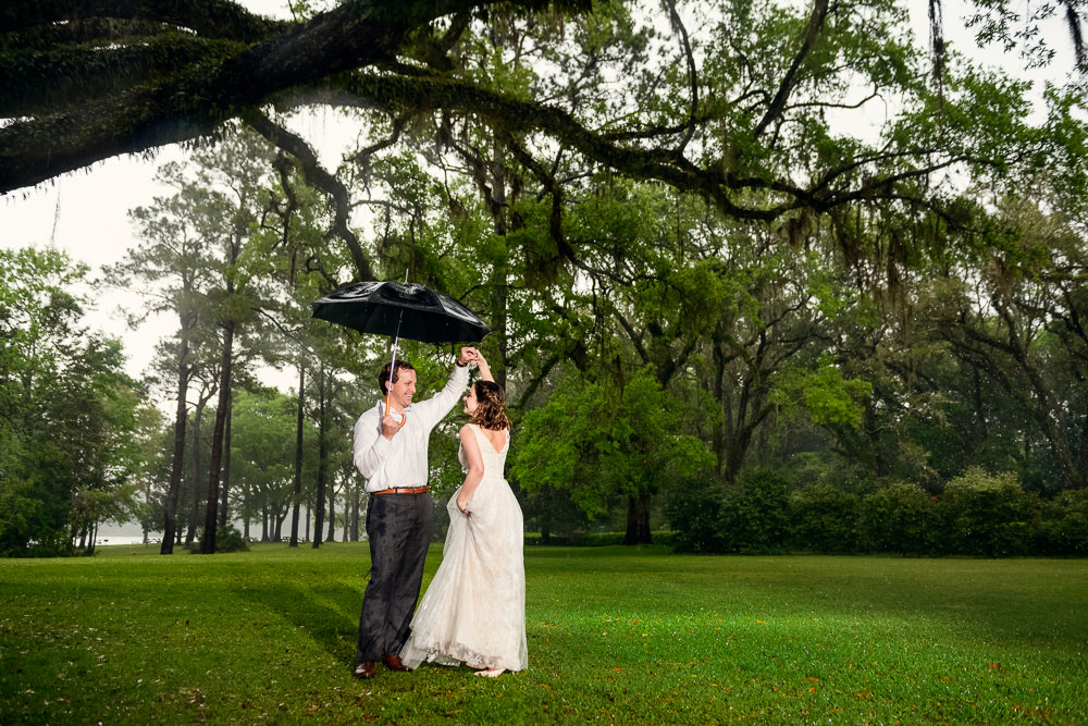 Couple dancing under umbrella in the rain, Fun Engagement Session at Eden Garden and Fort Pickens, Lazzat Photography, engagement photos