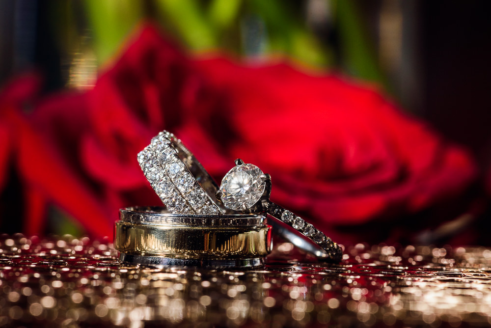 Bride and Groom's wedding rings stacked in front of red roses at the Rails on Wright Street, Classic Red and White Wedding, Lazzat Photography, wedding photography, wedding photographer