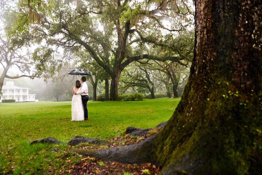 Couple looking away under umbrella in the rain, Fun Engagement Session at Eden Garden and Fort Pickens, Lazzat Photography, engagement photos