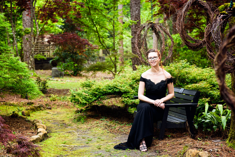 Taylor sitting on the bench in her black gown, Beautiful Mobile Botanical Gardens Engagement Session, Lazzat Photography