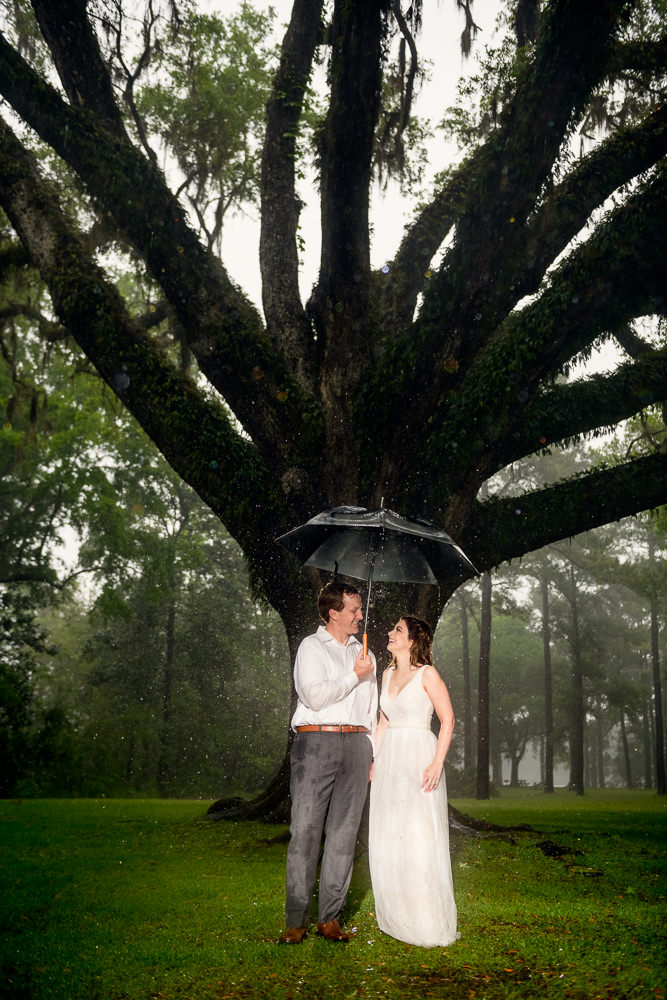 Couple under umbrella in the rain, Fun Engagement Session at Eden Garden and Fort Pickens, Lazzat Photography, engagement photos