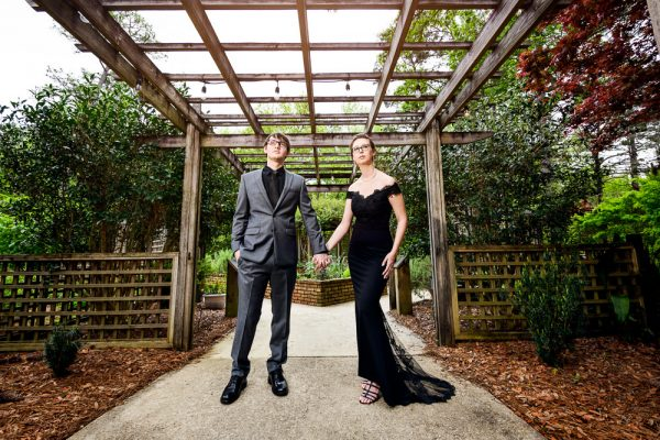 Taylor and Bob holding hands under a wooden lattice, Beautiful Mobile Botanical Gardens Engagement Session, Lazzat Photography