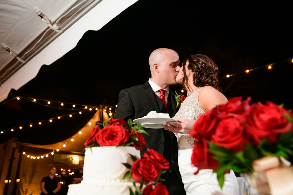 Bride and Groom kissing after feeding each other wedding cake at the reception at the Rails on Wright Street, Classic Red and White Wedding, Lazzat Photography, wedding photography, wedding photographer