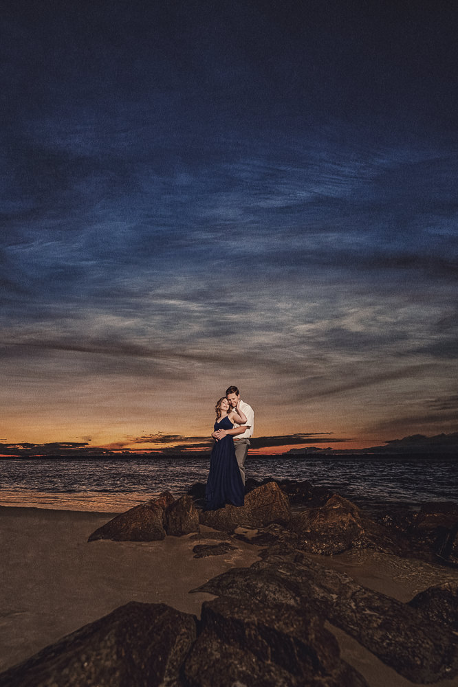 Couple hugging by the rock on the beach at sunset, Fun Engagement Session at Eden Garden and Fort Pickens, Lazzat Photography, engagement photos
