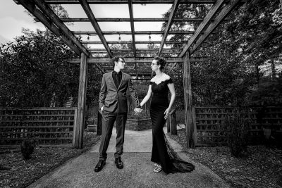 Taylor and Bob holding hands under a wooden lattice, black and white, Beautiful Mobile Botanical Gardens Engagement Session, Lazzat Photography