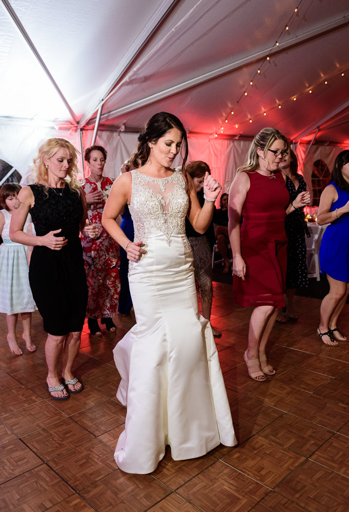 Bride line-dancing with guests during the reception at the Rails on Wright Street at night, Classic Red and White Wedding, Lazzat Photography, wedding photography, wedding photographer