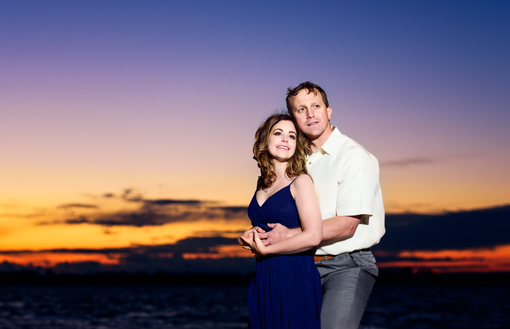 Couple hugging and looking into the distance at sunset, Fun Engagement Session at Eden Garden and Fort Pickens, Lazzat Photography, engagement photos