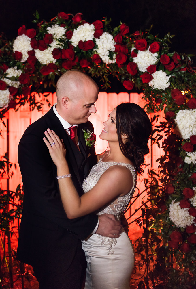 Close up of Bride and Groom in front of their wedding arch at the Rails on Wright Street at night, Classic Red and White Wedding, Lazzat Photography, wedding photography, wedding photographer